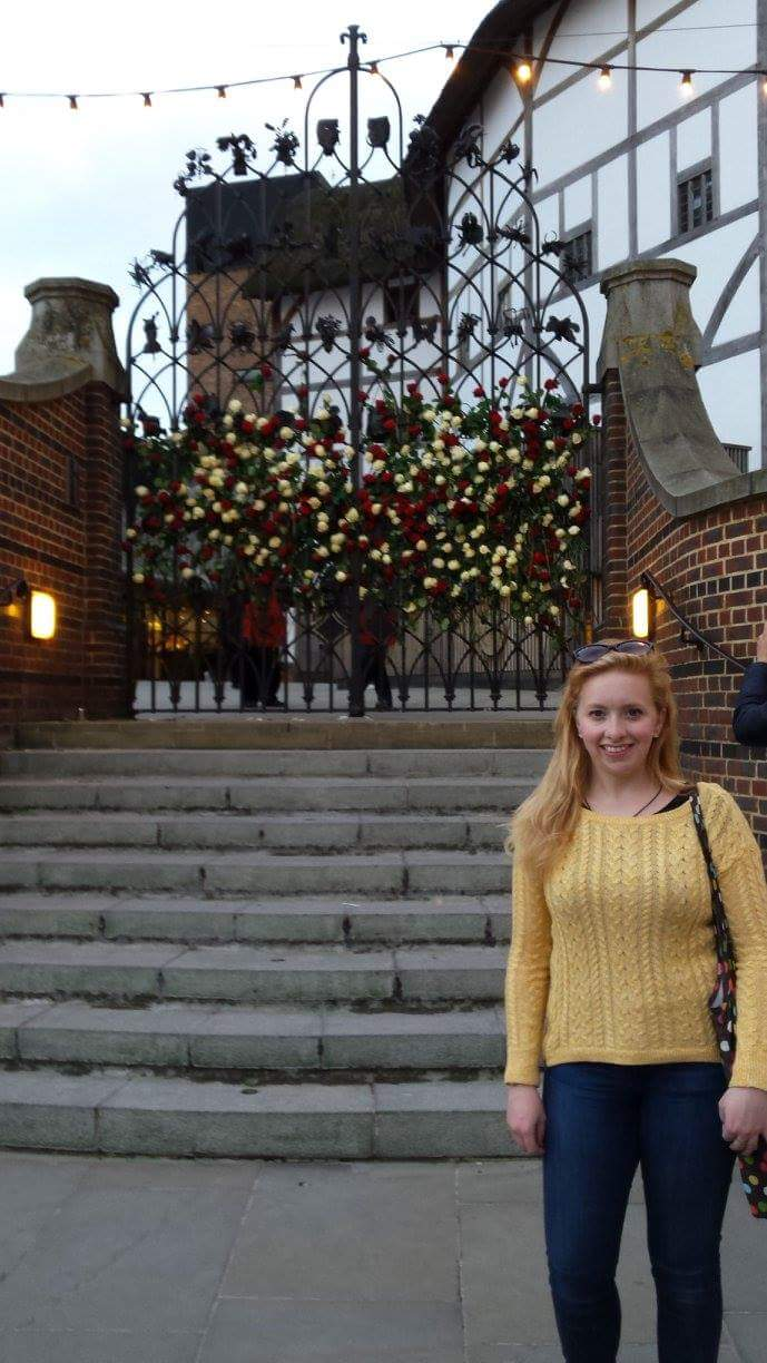 Jasmine outside the Globe Theatre with the gate full of roses. Picture from Jasmine.